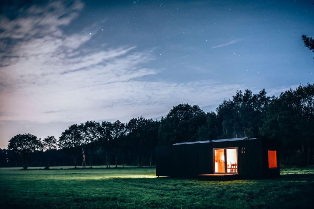 tiny house in der dämmerung mit erleuchteten fenstern